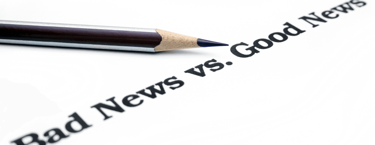 Bad news vs good news written in black on white paper with a pencil above the words