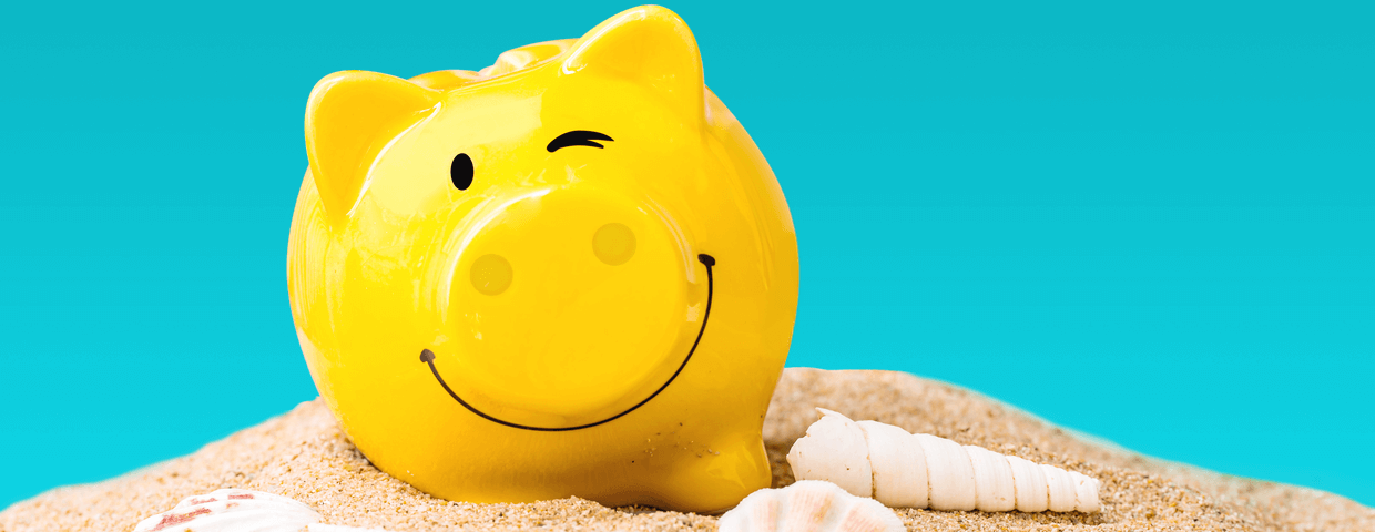Yellow smiling and winking piggy bank on top of sand and sea shells with blue background