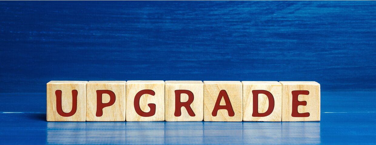 Wooden blocks that spell out the word upgrade in red letters on a blue surface with a blue background