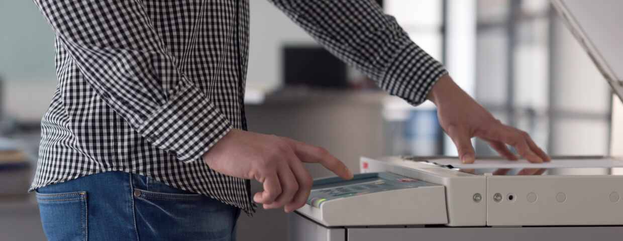 Man using multifunction scanner machine in office setting