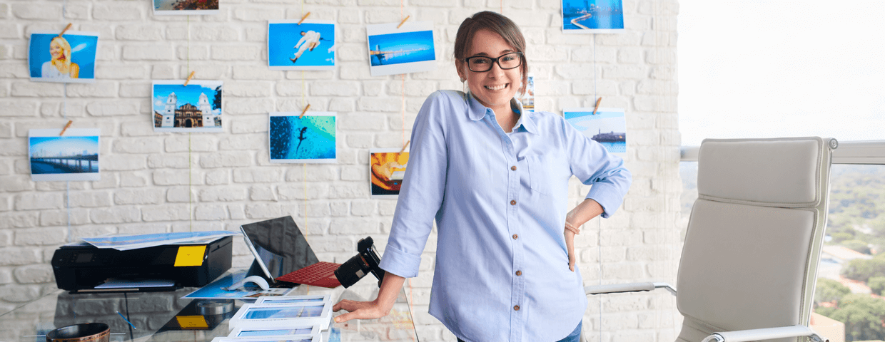 Small business owner, woman standing, smiling in office space.