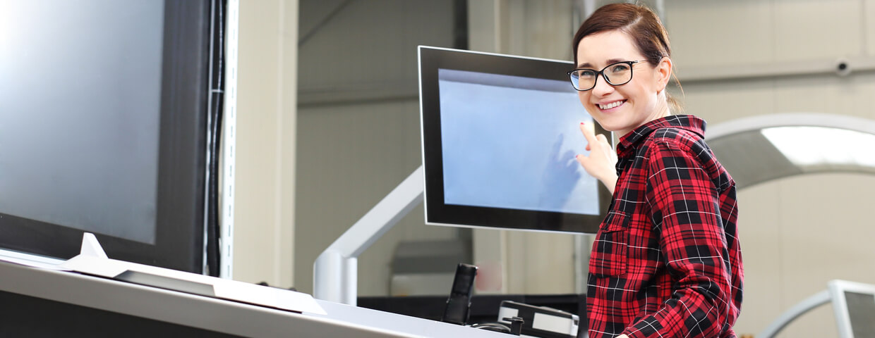 Woman smiling next to printer in office